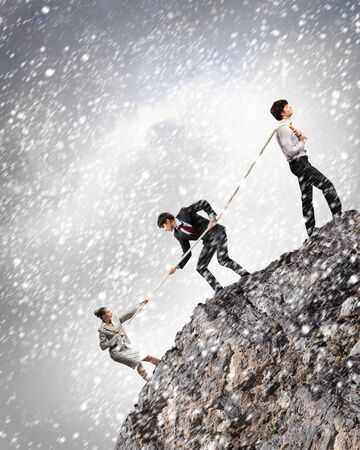pulling rope: Image of three businesspeople pulling rope atop of mountain under falling snow Stock Photo