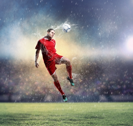 football player in red shirt striking the ball at the stadium under rain photo
