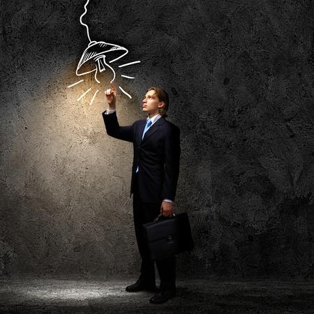 暗い背景に対して黒スーツのビジネスマンのイメージ 写真素材