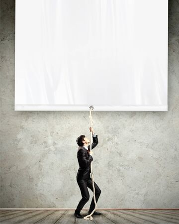 Image of young businessman pulling blank banner  Place for text photo