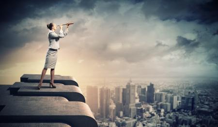 business: Bild av affärskvinna i teleskop står en upp i byggnaden Stockfoto
