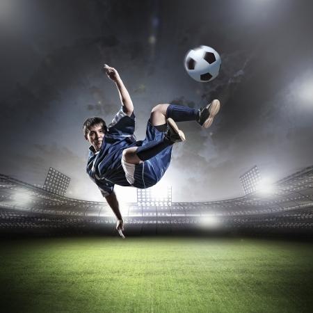 Image of football player at stadium hitting ball