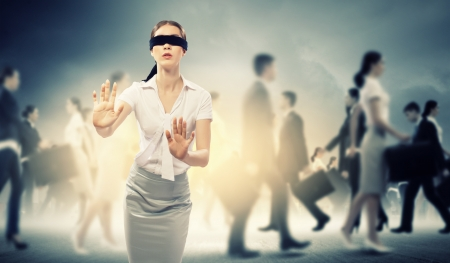 sightless: Image of businesswoman in blindfold walking among group of people