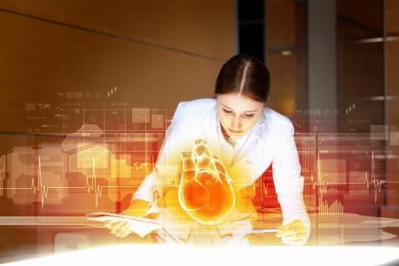 Immagine di donna attraente cardiologo esaminando cuore virtuale