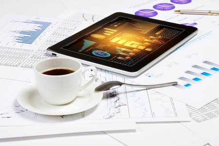 Image of cup of coffee and tablet laying on business documents photo
