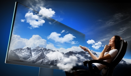 watch: Image of young woman in armchair watching 3d tv Stock Photo