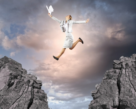 Image of young businesswoman jumping over gap photo