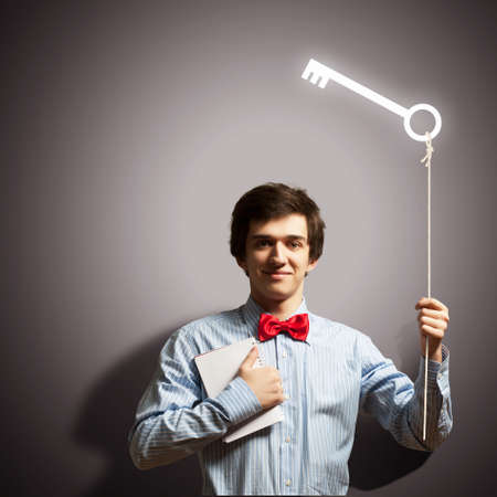 Image of young handsome businessman holding key photo