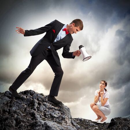 Angry businessman with megaphone shouting at colleague Stock Photo - 21151035