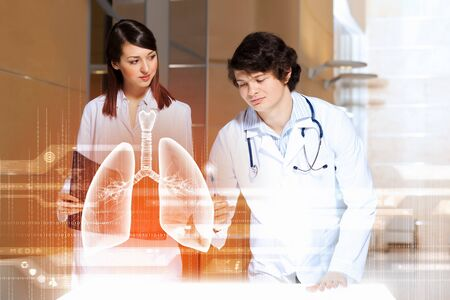 Image of two young doctors examining virtual image of lungs photo