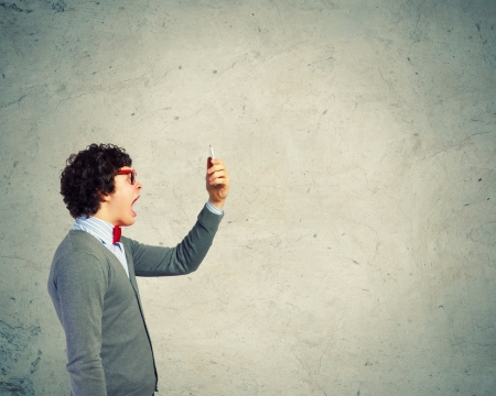 Young businessman with a red tie shouting furiously at his mobile phone Imagens