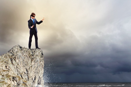 Image of businessman in blindfold standing on edge of mountain photo