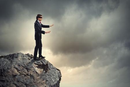 Beeld van zakenman in blinddoek staat op de rand van de berg