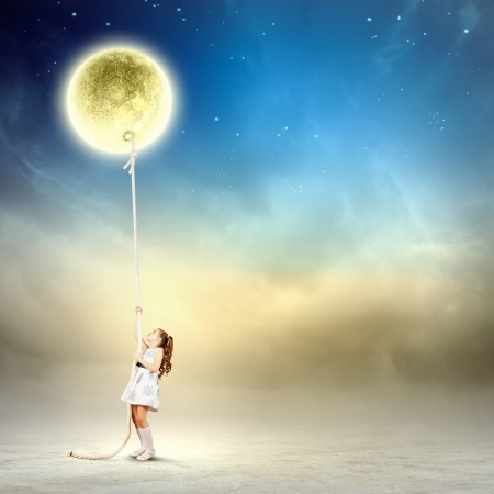 catch up: Image of little girl in white dress pulling moon Stock Photo