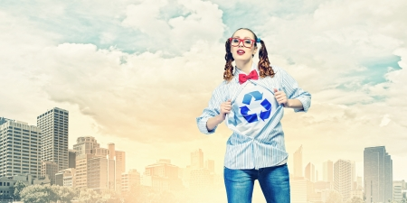 Young woman acting like super hero with recycle sign on chest photo