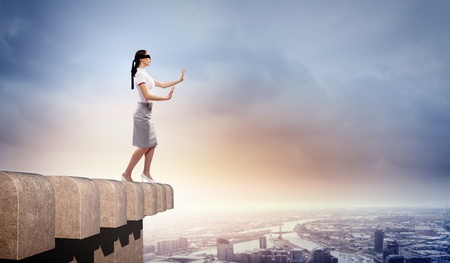 Image of businesswoman in blindfold standing atop of building photo