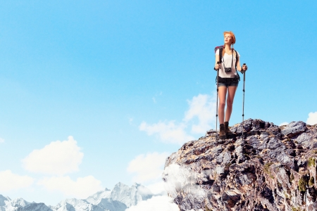 Pretty young woman tourist standing on top of mountain photo