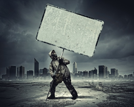 Stalker in gas mask with blank banner  Disaster concept photo