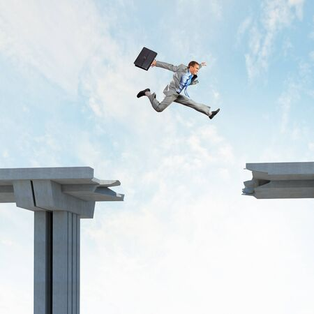 interrupted: Businessman jumping over a gap in the bridge as a symbol of bridge Stock Photo