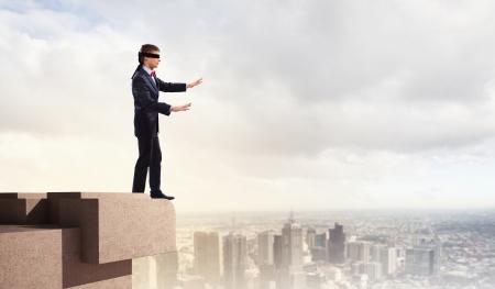 Afbeelding van zakenman in blinddoek staande op de top van het gebouw