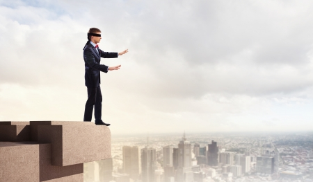 disoriented: Image of businessman in blindfold standing on top of building Stock Photo