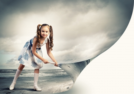 Little girl turning page with another reality photo
