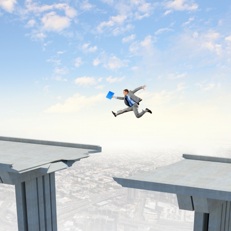 Businessman jumping over a gap in the bridge as a symbol of bridge Stock Photo