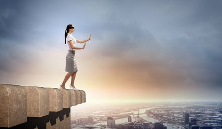 disoriented: Image of businesswoman in blindfold standing atop of building