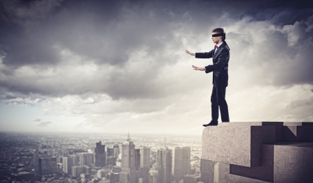 Image of businessman in blindfold standing on top of building photo