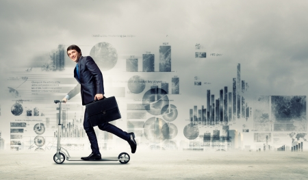 context: Image of young businessman in black suit riding scooter Stock Photo