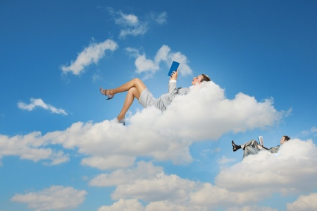 daydreaming: Image of businesspeople lying on clouds with tablet pc