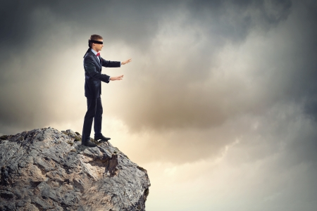 disoriented: Image of businessman in blindfold standing on edge of mountain Stock Photo