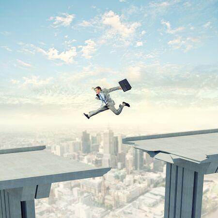 work hard: Businessman jumping over a gap in the bridge as a symbol of bridge Stock Photo