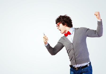 Young businessman with a red tie shouting furiously at his mobile phone photo