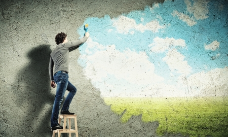 freedom nature: Young man drawing a cloudy blue sky on the wall