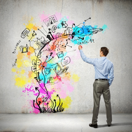 Back view of businessman drawing colorful business ideas on wall Stock Photo