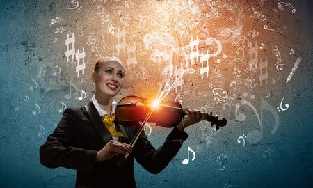Image of young smiling businesswoman playing violin photo