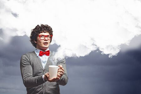 Young man with smoke coming out of a cup experimenting