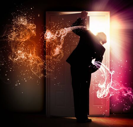 Image of young businessman standing with back opening door against smoke background photo