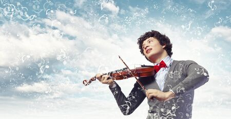 Image of young handsome man playing violin photo
