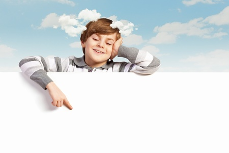 Little boy holding a blank white billboard photo