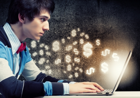 make an investment: Image of young businessman at work using laptop Stock Photo