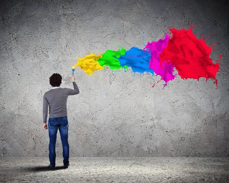 Young man spraying colour paints over background photo