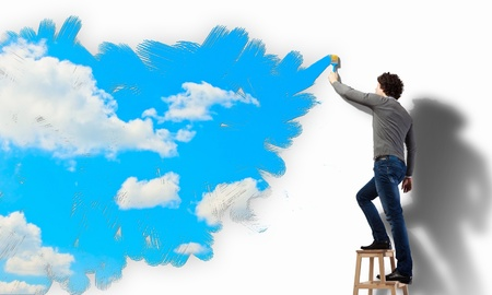 Young man drawing a cloudy blue sky on the wall photo