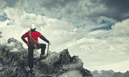 岩の頂上に立っている青年登山家のイメージ 写真素材