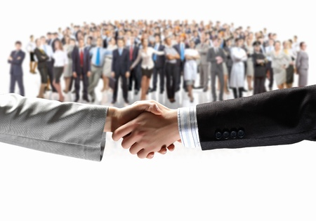 hired: Close-up of human handshake with crowd of people at background Stock Photo