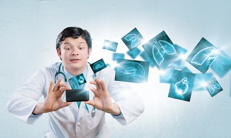 Young funny doctor taking photos with mobile phone camera photo