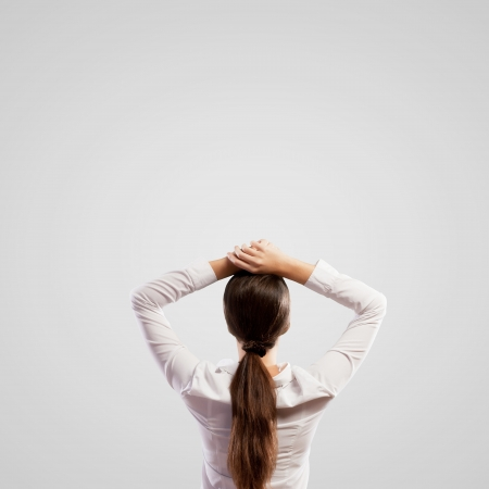 above head: Image of young woman standing with her back with arms above head  Place for text
