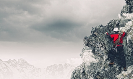 free climbing: Image of young man mountaineer standing atop of rock