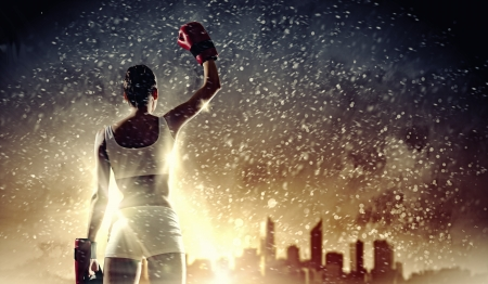 Young pretty boxer woman standing against city background photo